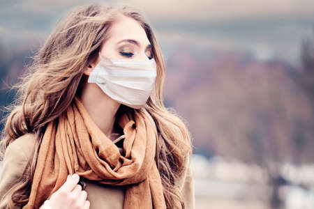 Pretty woman in medical protective face mask outdoors