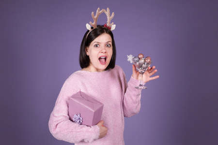 Happy surprised woman with Xmas gift box on purple background. Christmas and New Year concept Zdjęcie Seryjne