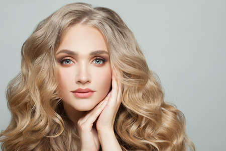 Lovely woman model face with long healthy blonde curly hair on white