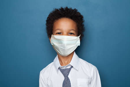 Portrait of cute black child boy in medical protective face mask