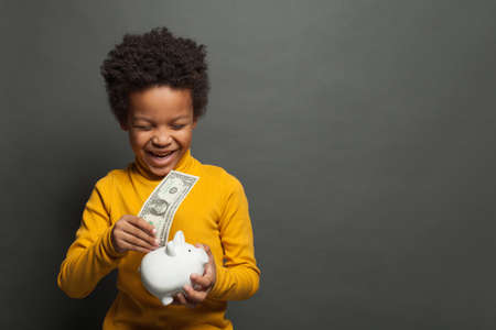 Happy successful African American child with money box and one us dollar on blackboard background Stock fotó
