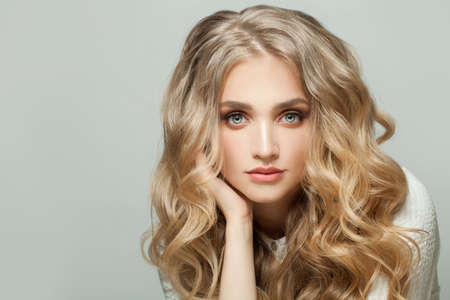Perfect blonde woman with healthy curly hairstyle on white