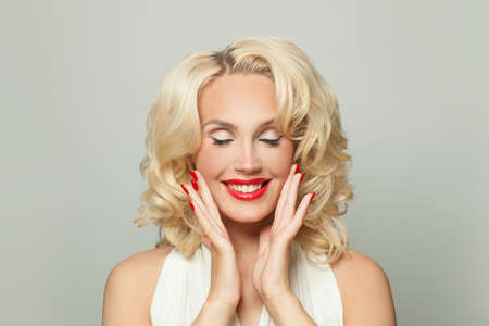 Celebrity woman with makeup and red manicured nails on white, fashion portrait