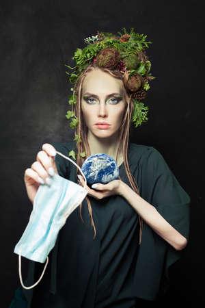 Environmental protection concept. Woman with used single-use face mask during COVID-19 and holding Earth Stok Fotoğraf