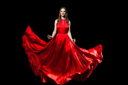 Beautiful fashionable woman wearing red silky dress isolated on black background