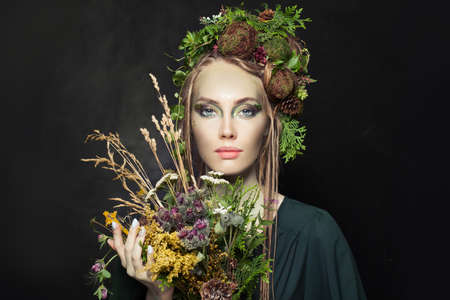 Nymph woman with wild flowers on black background