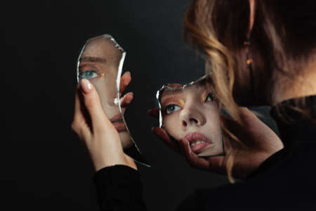 Perfect woman looking at broken self-image mirror on black background