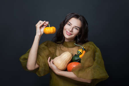 Happy woman with pumpkins on black background