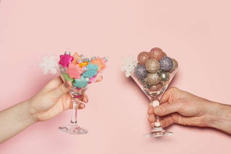 Christmas minimal background. Christmas toasting. Xmas decoration in couple hands on pastel pink background 版權商用圖片