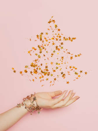 Christmas tree made from golden confetty stars on pink background. Minimal Christmas card 版權商用圖片
