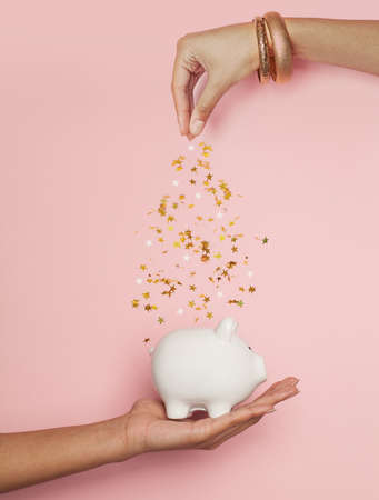 Black woman hands putting in money box golden confetti stars on pastel pink background