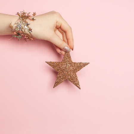 Christmas decoration card. Gold star in female hand on pink background 版權商用圖片