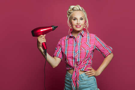 Pin-up woman using hairdryer posing on pink background