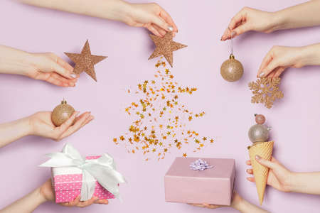 Christmas composition background. Many hands holding Xmas gifts and decorations on pastel purple color