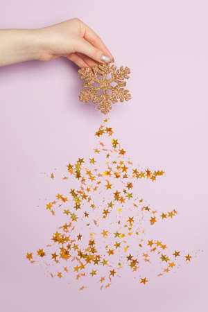 Snowflake and Christmas tree made from golden confetty stars on purple background. Minimal Christmas card composition