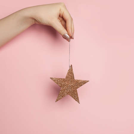 Christmas card with gold star in woman hand on pink background