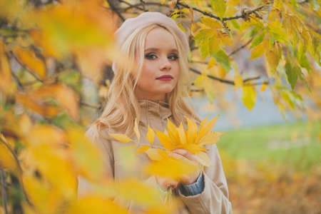 Beautiful woman holding autumn yellow leaves outdoors on fall nature background