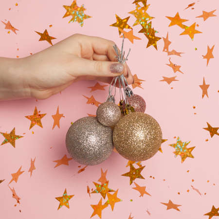Christmas or New Year confetti stars and Xmas balls in woman hand on pink card background