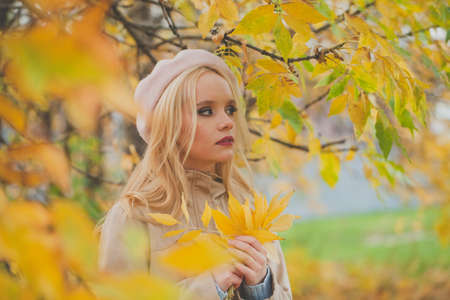 Autumn woman with yellow leaves on fall nature background 版權商用圖片