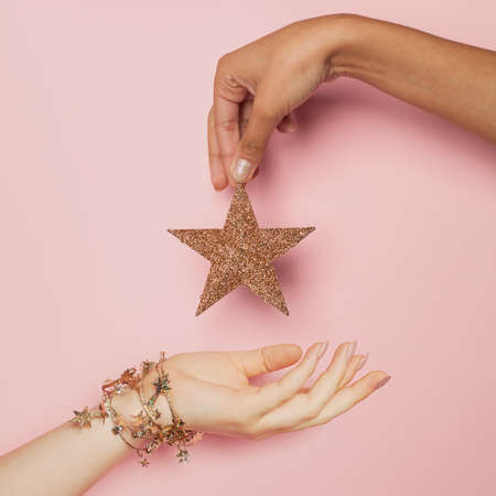 Christmas holiday concept. Black and white friends woman hands with gold Xmas decoration star on pink background