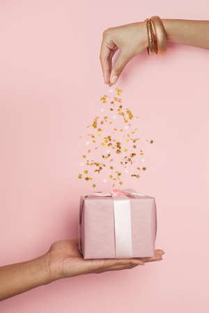 Pink gift and falling confetti on pastel pink, minimal background composition