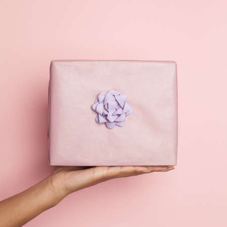 Female hand holding gift on pastel pink, minimal background composition card