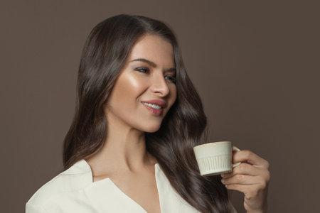 Pretty woman enjoying espresso coffee on brown background