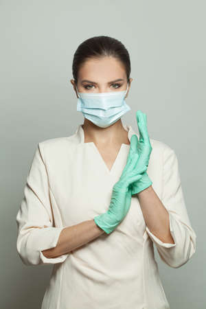Doctor surgeon woman in protective medical mask and surgical gloves on white background Zdjęcie Seryjne