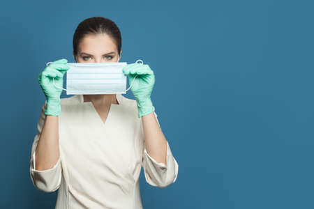Smart doctor showing protective medical mask on blue background. Medicine, safety and virus covid-19 protection concept