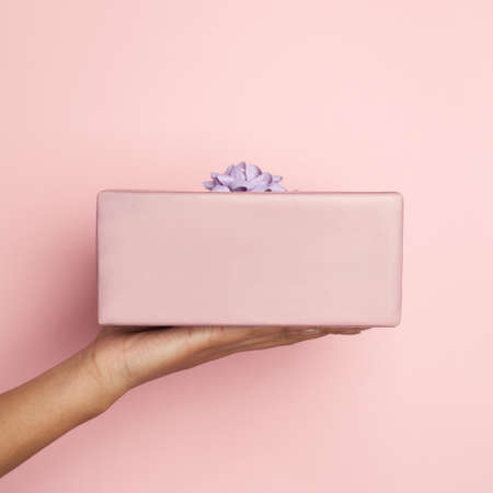Pink gift in woman hand on pastel pink, minimal background composition card