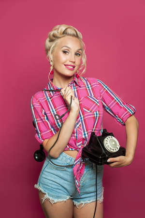 Cute pinup woman holding retro phone. Beautiful model with pink lips makeup and old fashion hairstyle