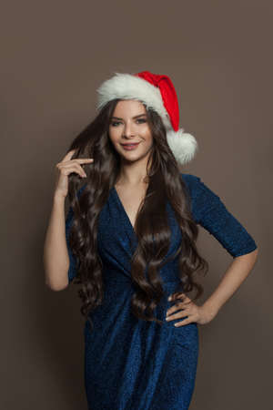 Pretty woman in Santa hat standing on brown background. Christmas holiday and New Year party