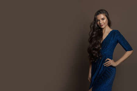 Perfect young model woman in blue shiny evening gown posing on brown banner background