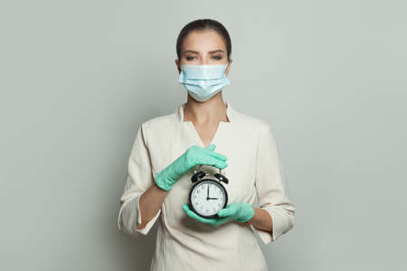 Doctor woman with alarm clock on white background
