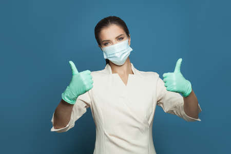 Happy doctor holding thumb up on blue background. Medicine, safety, vaccination and virus covid-19 protection concept
