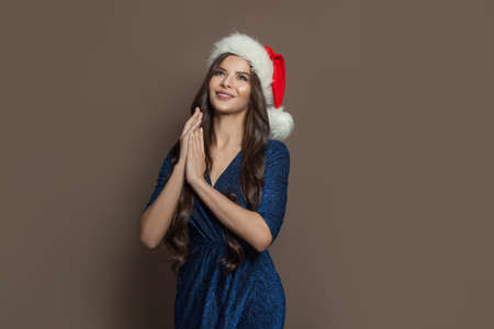 Cheerful woman Santa on brown banner background. Christmas holiday and New Year party portrait