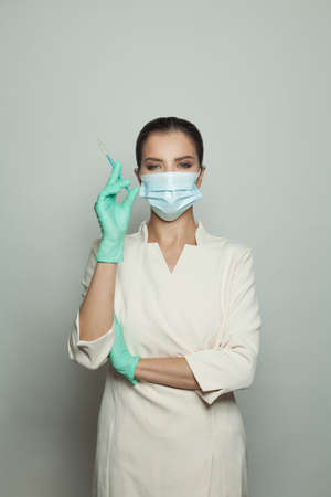 Optimistic doctor woman with syringe on white. Medicine, cosmetology and vaccination concept