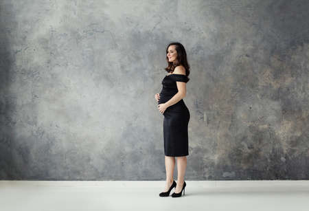 Pregnant woman in black dress standing on gray banner background