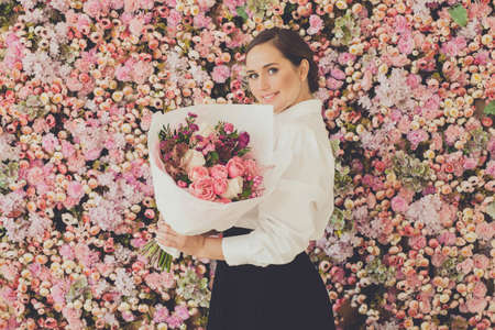 Happy woman with bouquet of flowers on pink roses floral blossom background