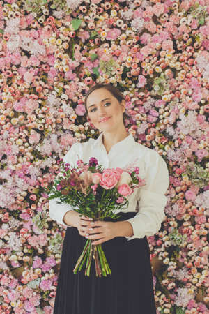 Pretty woman with flowers on floral blossom roses background 写真素材