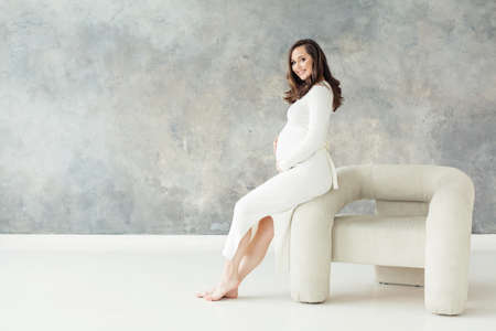 Pretty pregnant woman sitting on armchair on gray banner background