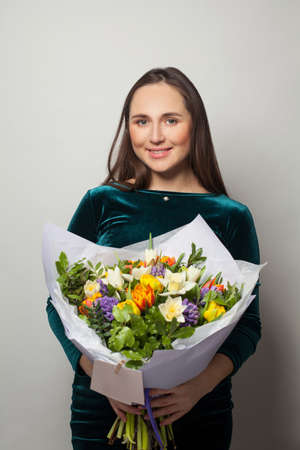 Cute smiling woman with flowers on white background 写真素材