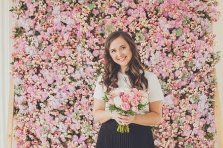 Cute woman smiling and holding pink and white rose flowers on floral spring blossom background 写真素材