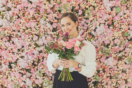 Happy smiling woman holding bouquet of flowers on pink roses floral blossom background 写真素材 - 166879585