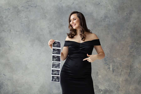 Pregnant woman pointing at her tummy and showing ultrasound scan image on gray Banque d'images