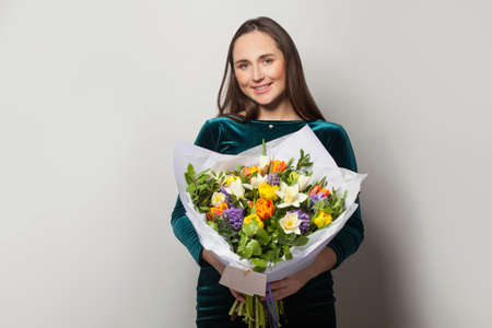 Portrait of attractive woman with flowers on white background