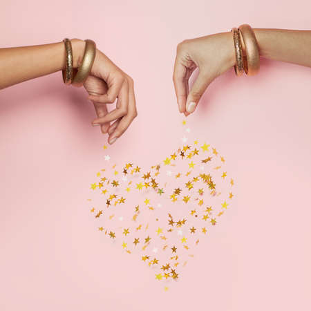 Female hands and falling confetti star. Heart on pink background 写真素材
