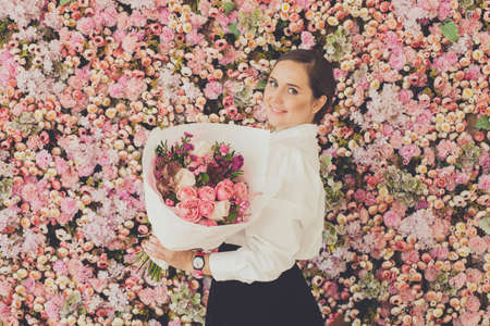 Smiling woman holding bouquet of flowers on pink roses floral blossom background 写真素材