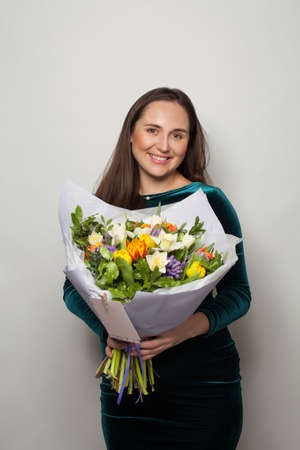 Cute smiling woman holding flowers on white background