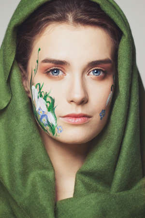 Spring woman with painted flowers on her face wearing green shawl 写真素材
